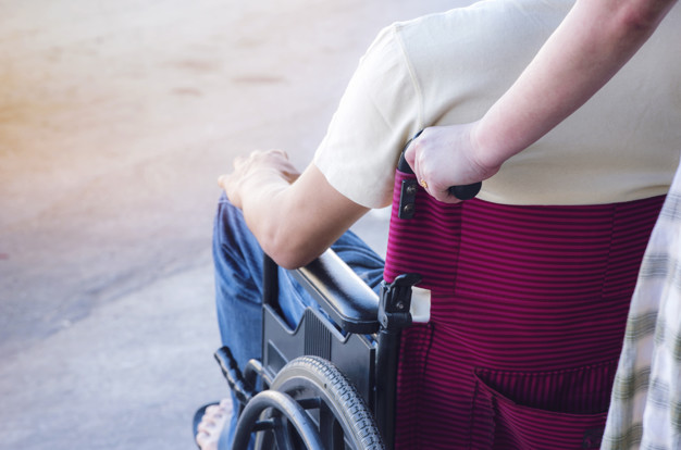 woman pushing wheelchair with men patient,wife is taking care of